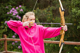 Concentrating blonde practicing archery
