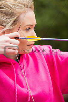 Focused blonde practicing archery