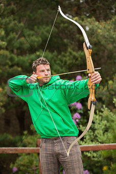 Focused man practicing archery