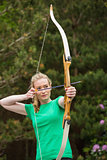 Concentrating blonde woman practicing archery