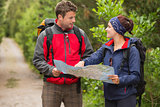 Smiling couple going on a hike together looking at map
