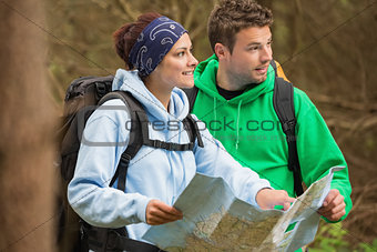 Smiling couple standing in a forest holding map