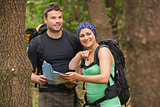 Fit couple reading map in a forest with woman pointing