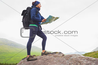 Woman standing on a rock holding map