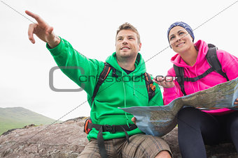 Couple using map and compass sitting on a rock with man pointing
