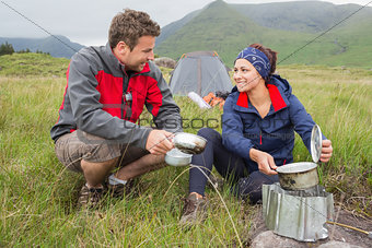Couple cooking outside on camping trip and smiling