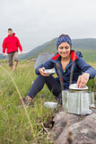 Woman cooking outside on camping trip with boyfriend walking