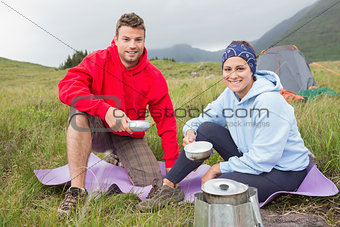 Couple cooking outside on camping trip smiling at camera