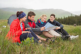 Friends sitting on grass and looking at map on camping trip