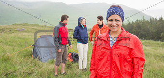 Brunette smiling at camera with friends behind her on camping trip