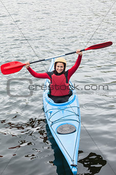 Happy woman in a kayak cheering at the camera