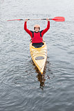 Happy man in a kayak cheering at camera