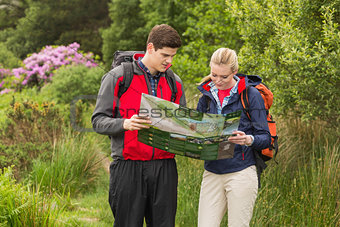 Sporty couple on a hike looking at map