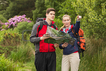 Sporty couple on a hike holding map and pointing