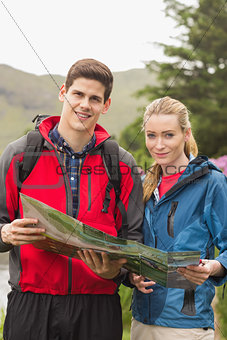 Happy couple holding map on a hike