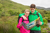 Athletic couple in hooded jumpers on a hike reading map