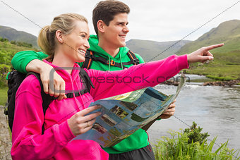 Athletic couple in hooded jumpers on a hike holding map