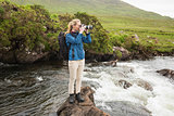 Blonde woman standing on a rock in a stream taking a photo