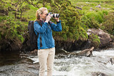 Blonde standing on a rock in a stream taking a photo