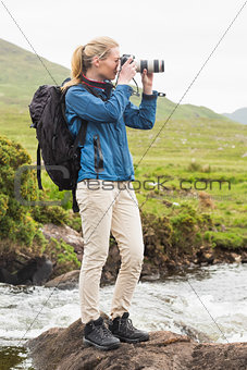 Blonde woman on a hike taking a photo