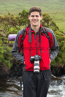 Handsome man on a hike with camera around his neck