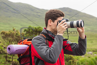 Sporty man on a hike taking a photograph