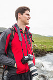 Brunette man on a hike with a camera around his neck