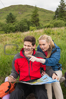 Cheerful couple taking a break on a hike to look at map with woman pointing