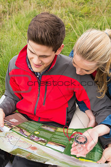 Cheerful couple taking a break on a hike to look at map and compass