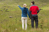 Couple holding hands with woman pointing on a walk