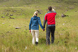 Couple holding hands on walk with man pointing