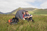 Couple sitting in their tent after a hike