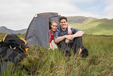 Couple sitting in their tent after a hike and smiling at camera