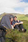 Happy couple sitting in their tent after a hike and looking at camera