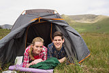 Happy couple lying in their tent after a hike and looking at camera