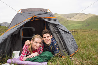 Happy couple lying in their tent and looking at camera