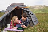 Happy couple lying in their tent and using digital tablet