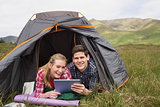 Smiling couple lying in their tent and using digital tablet