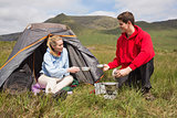 Cheerful couple cooking outdoors on camping trip