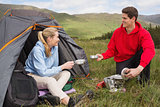Happy couple cooking outdoors on camping trip