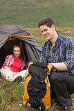 Man packing backpack while girlfriend sits in tent