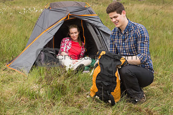 Happy man packing backpack while girlfriend sits in tent