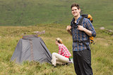 Smiling man carrying backpack while girlfriend is pitching tent