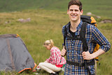Cheerful man carrying backpack while girlfriend is pitching tent