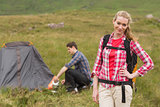 Cheerful woman carrying backpack while boyfriend is pitching tent