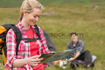 Happy woman carrying backpack and holding map