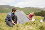 Happy couple pitching their tent