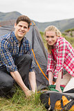 Happy couple pitching their tent together