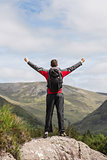 Man standing at hill top cheering