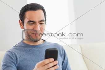 Smiling casual man text messaging
